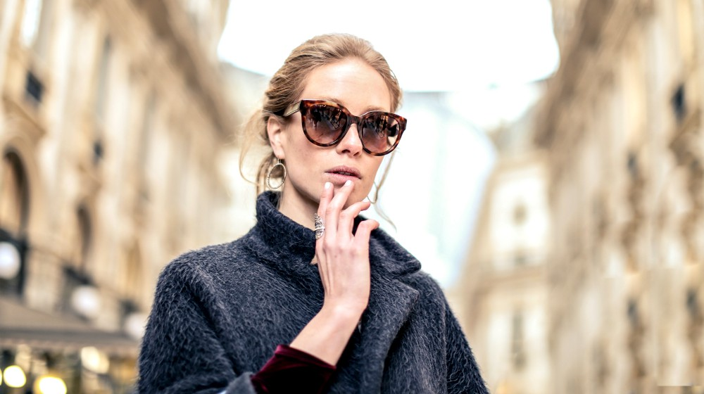 woman wearing black coat and brown framed sunglasses | Habits That Help Prevent Wrinkles | Featured