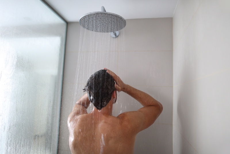 Man taking a shower washing hair under water falling from rain showerhead. Showering person at home lifestyle. Young adult body care morning routine. | balanitis causes