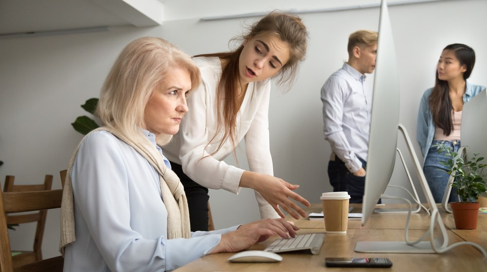 Young team leader correcting offended senior employee working on computer in office, scolding aged old worker |age discrimination | ageism in the workplace