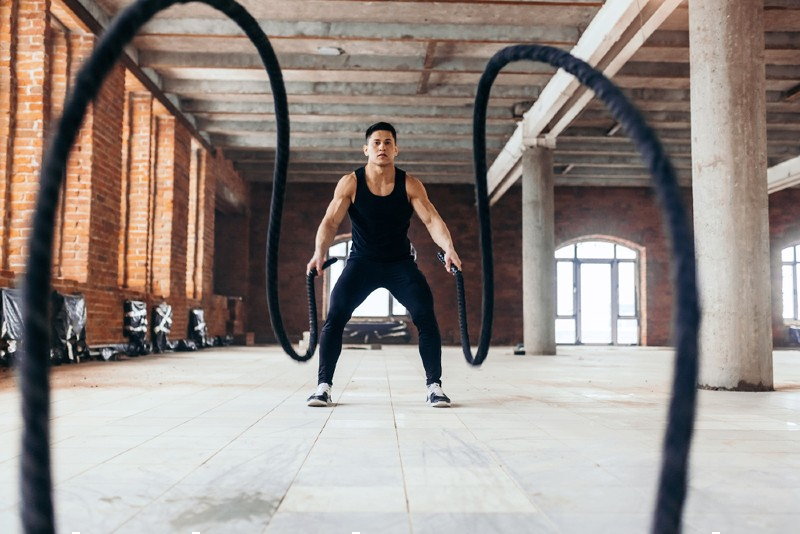 strong young man moving ropes gym | battle ropes hiit workout