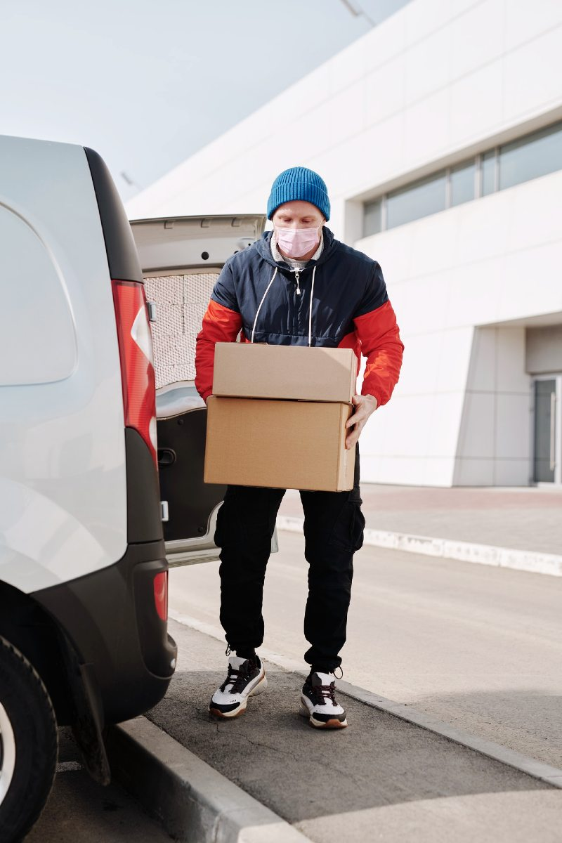 delivery man wearing a face mask carrying boxes | tips for downsizing for seniors