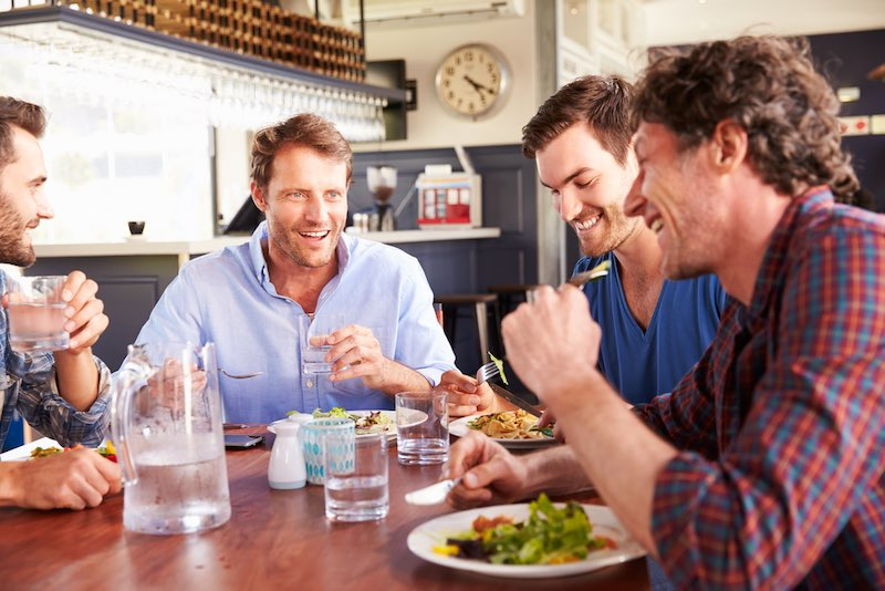 A group of friends having lunch in a restaurant | Amazing Benefits Of Turning 50