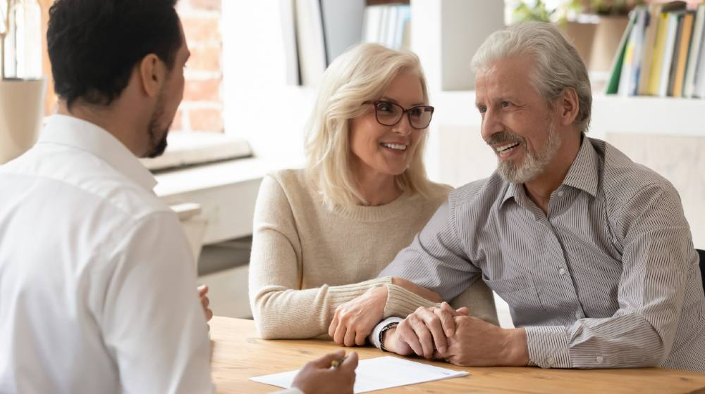 Diverse people sit at desk in office, male realtor make property offer for sale to elderly spouses old customers contract lie on table | Retirement Planning For The 21st Century | Featured