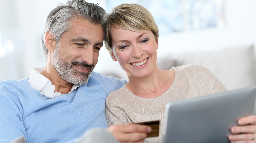Cheerful mature couple e-shopping on internet | Senior Discounts and Perks You Can Enjoy When You Turn 50 | Featured