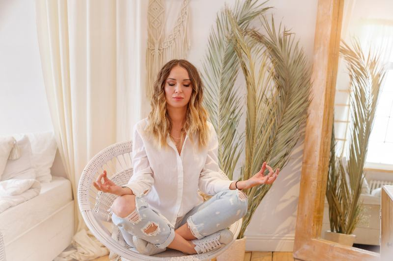 Blonde european female wearing a white shirt and jeans meditating in lotus position-Improve Your Memory
